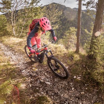 Eine Frau fährt mit einem Conway E-Mountainbike auf einem Singletrail.